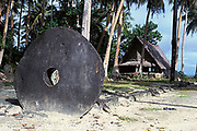large piece of stone money in <br /> front of meeting house, Yap,<br /> Federated States of Micronesia,<br /> ( Western Pacific Ocean )