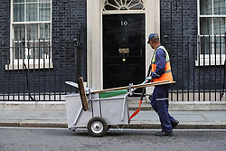 A street sweeper walks past 10 Downing Street, London, as Theresa May's future as Prime Minister and leader of the Conservatives was being openly questioned after her decision to hold a snap election disastrously backfired.
