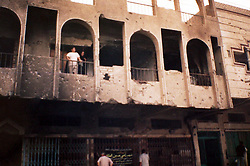 Photograph of the shrapnel riddled building where Salah Izat resides, taken in March 2003, Baghdad, Iraq, March 2, 2004. Salah Izat's home was destroyed when an American missile hit just outside their front door. A year later, Izat is getting better pay wages, but has lost his right leg from diabetes. He says the lack of medical resources after the war made him unable to get proper attention for his ailing leg, possibly being the reason it became so  gangrenous that it had to be amputated.