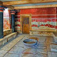 Knossos. Crete. Greece. View of the Throne Room located on the ground floor of the Palace of Knossos west wing. The room has the throne of Minos made of gypsum standing against the north wall flanked by guardian griffins frescoes and the original benches that seated sixteen noble counsellors. Opposite the throne are a row of wooden columns which provide a barrier to the small lustral basin which is reached by a number of steps and was used for sacred ablutions by the King and court.
