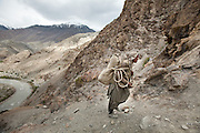 A Wakhi porter carrying a load, high above the Wakhan river. Trekking up and along the Wakhan river, the only way to reach the high altitude Little Pamir plateau, home of the Afghan Kyrgyz community.