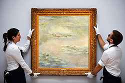"""© Licensed to London News Pictures. 14/06/2019. LONDON, UK. Technicians present """"Nymphéas"""", 1908, by Claude Monet (Est. £25-30m). Preview of Impressionist and Modern art sales, which will take place at Sotheby's New Bond Street on 18 and 19 June 2019.  Photo credit: Stephen Chung/LNP"""