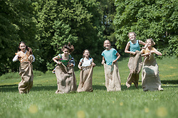 Group of girls jumping in sack race in a field, Munich, Bavaria, Germany