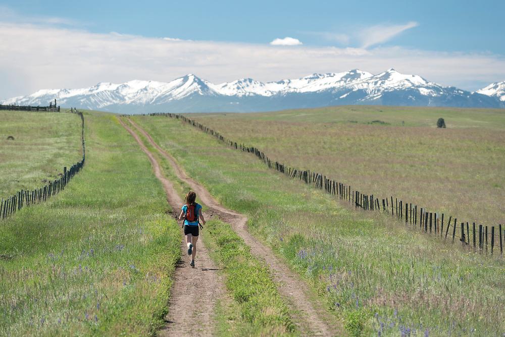 Woman running on a dirt road on the Zumwalt Prairie in Northeast Oregon.