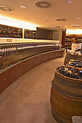 A curved display of bottles and a barrel used to present bottles The Lavinia wine shop in Paris. Probably the biggest wine shop in Paris, with its special temperature controlled section for wines that are fragile and must be stored at cool low temperature.