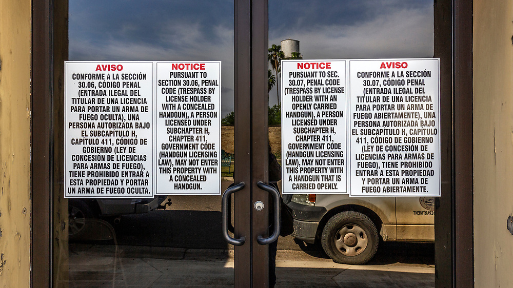 Signs on shop doorways prohibiting firearms to be carried onto the property. Roma, Texas, USA