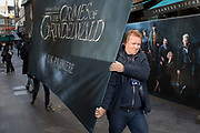 Contractors carry a publicity board for the new film Fantastic Beasts: The Crimes of Grindelwald, hours before its UK premier in Leicester Square, on 13th November 2018, in London, England.