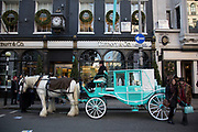 Horse and carriage outside Tiffany and Co. on Bond Street, London, UK. Exclusive shops on New Bond Street, Mayfair, central London. It is one of the principal streets in the West End shopping district and is more upmarket. It has been a fashionable shopping street since the 18th century. The rich and wealthy shop here mostly for high end fashion and jewellery.