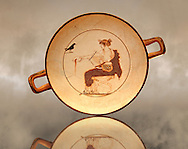 White Ground Kylix from a tomb in Delphi. Athenian 480-470 BC. Apollo depicted crowned in Myrtle Leaves, seated on a stool, with lion claw feet, dressed in a white peoples. In his left hand he has a liar and with his right hand he pours a libation from a naval-phiale. The Crow recalls his mythical love for the beautiful Aigle-Koroni, daughter of King Phlegyas. Delphi Archaeological museum. .<br /> <br /> If you prefer to buy from our ALAMY STOCK LIBRARY page at https://www.alamy.com/portfolio/paul-williams-funkystock/greco-roman-sculptures.html . Type -    Delphi     - into LOWER SEARCH WITHIN GALLERY box - Refine search by adding a subject, place, background colour, museum etc.<br /> <br /> Visit our ANCIENT GREEKS PHOTO COLLECTIONS for more photos to download or buy as wall art prints https://funkystock.photoshelter.com/gallery-collection/Ancient-Greeks-Art-Artefacts-Antiquities-Historic-Sites/C00004CnMmq_Xllw