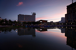 Stock photo of the reflection of the surrounding buildings in the park's pond at sunset