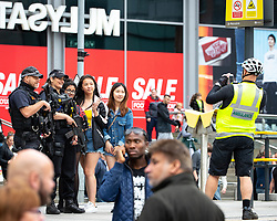 © Licensed to London News Pictures . 17/06/2018. Manchester , UK . Three girls pose for a photo with armed police in Exchange Square as the 2018 Manchester Day parade , celebrating Manchester's cultural and social life and diversity, passes through Manchester City Centre . Photo credit : Joel Goodman/LNP