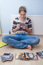 Teenage girl sitting on floor looking at her CDs at home,