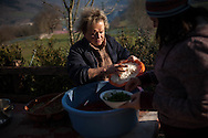 Mother and daughter prepare the collected blood to make blood sausages in traditional way pig slaughtering. Legasa (Basque Country). January 7, 2017. The slaughter traditionally takes place in the autumn and early winter and the work often is done in the open. (Gari Garaialde / Bostok Photo)