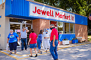 "03 AUGUST 2020 - JEWELL, IOWA: People come out of and go into the Jewell Market after the market's official grand reopening. The only grocery store in Jewell, a small community in central Iowa, closed in 2019. It served four communities within a 20 mile radius of Jewell. Some of the town's residents created a cooperative to reopen the store. They sold shares to the co-op and  held fundraisers through the spring. Organizers raised about $225,000 and bought the store, which had its ""soft opening"" July 8. The store celebrated its official reopening Monday August 3. Before the reopening, Jewell had been a ""food desert"" for seven months. The USDA defines rural food deserts as having at least 500 people in a census tract living 10 miles from a large grocery store or supermarket. There is a convenience store in Jewell, but it sells mostly heavily processed, unhealthy snack foods that are high in fat, sugar, and salt.         PHOTO BY JACK KURTZ"