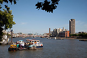 Scene of the River Thames, London. Running through the heart of the city. Barges boats and tugs with a view east.