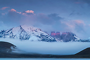 View of high snowcapped mountains under moody sky on winter day, Torres del Paine National Park, Chile