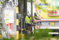 © Licensed to London News Pictures. 04/10/2021. London, UK. Workers are seen refuelling a fuel tanker at Buncefield oil depot in Hemel Hempstead, Hertfordshire. Military personnel are expected to start helping with driver shortages today following more than a week of long queues and closures at petrol stations. Photo credit: Ben Cawthra/LNP