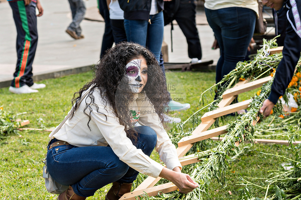 A young woman dressed in La Calavera Catrina costume arranges an floral alter for the Day of the Dead or Día de Muertos festival October 31, 2017 in Patzcuaro, Michoacan, Mexico. The festival has been celebrated since the Aztec empire celebrates ancestors and deceased loved ones.