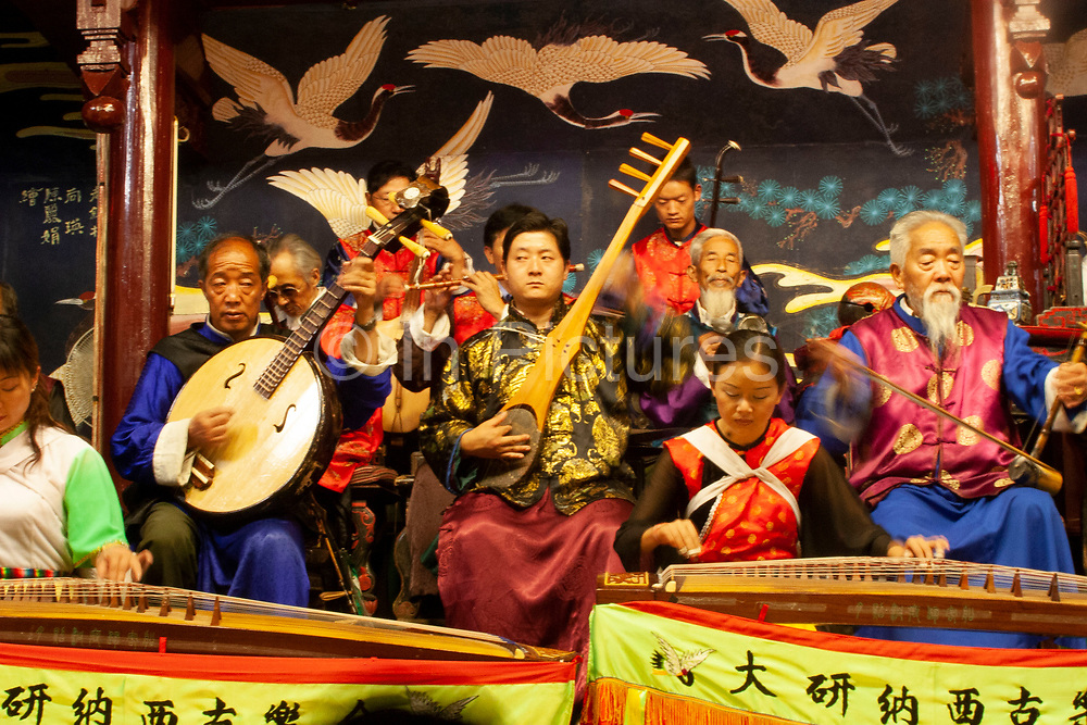 Elderly musicians in a Naxi Orchestra, a Naxi minority group playing at the Naxi Music Academy, Naxi Guyue Hui, in Old Town Lijiang, Yunnan province, China. The beautiful repetitive music they produce has been lost elsewhere in China and is threatened even here in Lijiang due to it's ageing players. The instruments played did not survive the Cultural Revolution in most parts of China, but several members of the Naxi group hid theirs by burying them, to revive them in 1978 after the revolution. Music from the Han, Tang, Song and Yuan Dynasties is played.