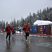 """Competitors warm up during the Bobsleigh Four-man competition  at The Whistler Sliding Centre, Whistler, during the Vancouver Winter Olympics. 26th February 2010. Photo Tim Clayton..'BOB'..Images from the Four-man Bobsleigh Competition. Winter Olympics, Vancouver 2010..History was made at the Whistler Sliding Centre when the USA four-man bobsleigh team, led by Steven Holcomb took the Gold. The first time since 1948, a gap of 62 years, since the USA have won an Olympic Bobsleigh gold and they did it with their sleigh named """"Night Train""""...The four days of practice and competition show the tension, nervousness and preparation as the teams of hardened men cope with the challenge of traveling at average speeds of over 150 km an hour. Indeed, five teams had already pulled out of the event before the opening heats because of track complexity, speed and fear, and on the final day, another four teams did not start after six crashes in the first two heats...Teams warm up behind the start complex, warming muscles in the cold in preparation for the explosive start. Many teams prepare in silence, mentally preparing themselves as they wait at the top of the run, in the bobsleigh sheds and the loading areas for their turn. When it's time to slide each team performs it's own starting ritual, followed by the much practiced start out of the blocks for just over four seconds, the teams are then in the hands of the accomplished drivers as they hurtle down the track for just over fifty seconds...Spectators clamber for the best position on track to see the sleighs for a split second, many unsuccessfully try to capture the moments on camera, The rumble of the sleigh is heard then the crowds gasp as it hurtles past in a blur...The American foursome of  Steven Holcomb, Justin Olsen, Steve Mesler and Curtis Tomasevicz finished with a pooled four-heat time of 3min 24.46sec. The German team led by Andre Lange won the Silver Medal in a combined time of 3min 24.84sec while the Bronze Medal went"""