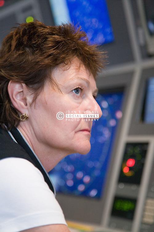 Air Traffic Control Tower Operator watching radar screens at East Midlands Airport,