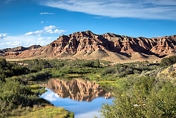 Spring Creek reflection, the painted hills of Dubois Wyoming reflect into a spring creek.  The Badlands of Dubois are quite the juxtaposition to the Absaroka Mountains a short distance away.