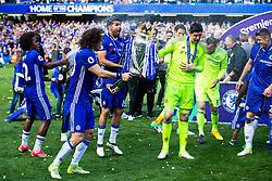 Willian and David Luiz spray champagne as Diego Costa and Thibaut Courtois lift the trophy as Chelsea celebrate winning the 2016/17 Premier League - Rogan Thomson/JMP - 21/05/2017 - FOOTBALL - Stamford Bridge - London, England - Chelsea v Sunderland - Premier League..