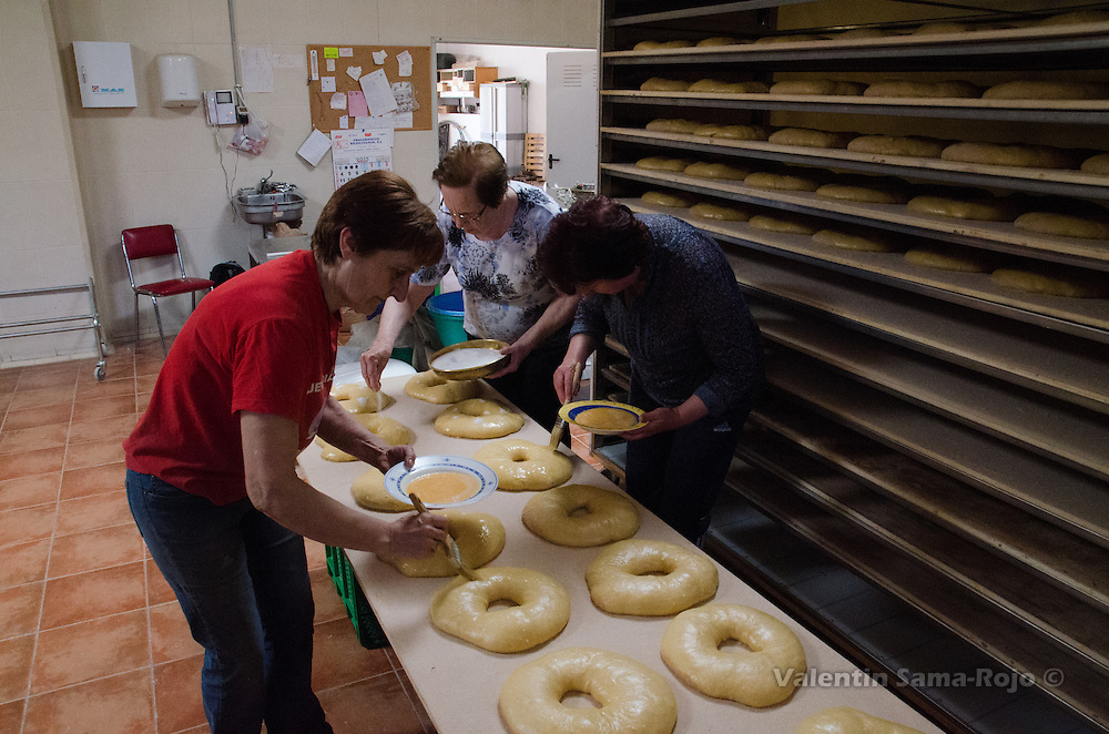 Women covering the top of the ring-shaped pastries with scrambled eggs and sugar.