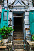 07 JUNE 2014 - YANGON, MYANMAR: The entrance to a residential building with shops on the ground floor on 22nd Street in Yangon. The building is one of a number of small colonial era buildings still in use in Yangon. This building, which doesn't have a name was opened in 1924. Yangon has the highest concentration of colonial style buildings still standing in Asia. Efforts are being made to preserve the buildings but many are in poor condition and not salvageable.    PHOTO BY JACK KURTZ
