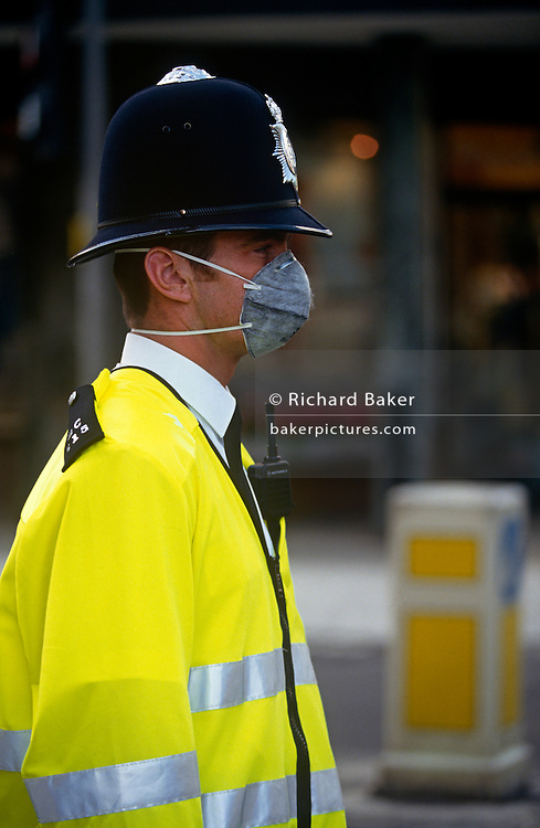A Met Police officer wears a pollution mask while in traffic in central London. With elastic ties reaching behind his head, the policeman breathes easier in the presence of microscopic background bacteria particles and NO2 gas levels found in areas of heavy traffic, in large UK cities. His work takes him out into polluted areas and the Police Federation insist on protecting its union members from atmospheric harm.