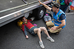 London, UK. 23rd August, 2021. Environmental activists from Extinction Rebellion use a lock-on under a vehicle to block a road in the Covent Garden area during the first day of Impossible Rebellion protests. Extinction Rebellion are calling on the UK government to cease all new fossil fuel investment with immediate effect. Credit: Mark Kerrison/Alamy Live News