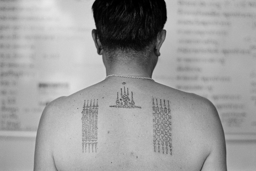 """Thailand is a deeply spiritual country, in which both superstition and ritual tattooing play an active role.   Traditional Thai tattoos are known as Yantra tattoos.  They are believed to possess strong magical powers, which will protect the bearer as well as bring him or her good luck.  With their alleged ability to break knife blades and stop bullets, this form of tattooing is particularly favoured by soldiers and the police force as well as, inevitably, by members of the underworld.<br /> <br /> Thai culture is a rich mixture of many Asiatic religious traditions.  It encompasses Hinduism, Brahmanism, Animism and Buddhism.  Whilst being ingrained in Hindu culture, Yantra tattoos, known also in Thailand as """"Sak Yant"""", incorporate many elements from these other belief systems.  A further influence is taken from ancient Khmer Sanskrit texts, many of which are believed to possess magical powers. Yantra or Sak Yant tattooing is a widely practised form of sacred tattooing prevalent throughout Southeast Asia.  Adepts are to be found mainly in Cambodia, Laos and Thailand, although there is a growing interest in Singapore among Chinese Buddhists.  Sak Yant is usually performed by a """"whicha"""" (magic) practitioner.  <br /> <br /> Today the best-known temple for Yant or Sak Yant tattooing is Wat Bang Phra.   This temple has an unbroken tattooing tradition dating back to the Ankor period.  The motifs and designs have evolved over the centuries, often as the result of visions received during sessions of intensive meditation.  <br /> <br /> Many Yant tattoos have been taken from images pertaining to pre-Buddhist Shamanism and its belief in multiple animal spirits. Most of these animalistic images come from the Southeast of the Asian sub-Continent and have subsequently been incorporated into Thai traditions and culture. The writing used in Yant designs is ancient Khmer"""