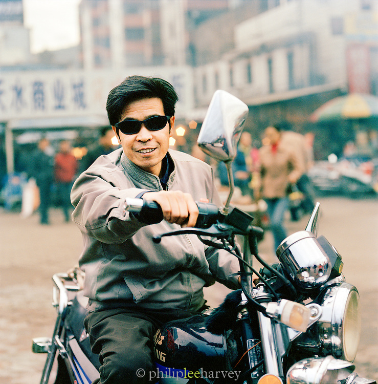Man on a motorcycle in the streets of Tianshui, Gansu province, China
