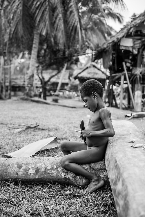 A boy named Fredron shaves pieces off a stick using a machete in Yar, a village on the Keram River in Papua New Guinea's East Sepik Province