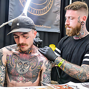 Matt Edwards TattooER, Tattoo a client at The Great British Tattoo Show, on 26 May 2019, London, UK.