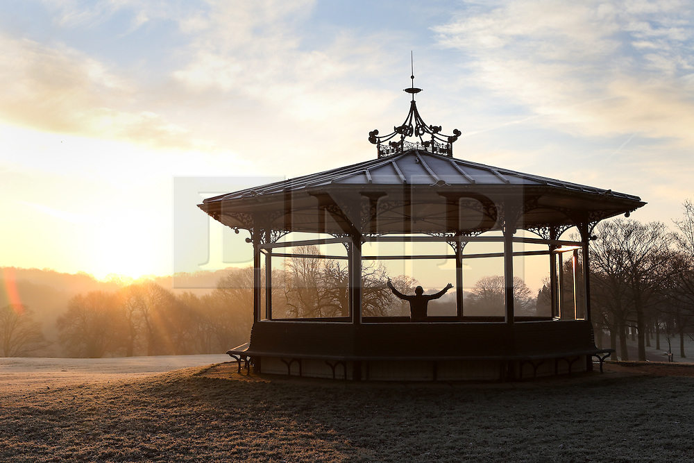 © Licensed to London News Pictures. 24/01/2017. Leeds, UK. A runner stretches inside the bandstand as the sun rises on a bitterly cold and frosty morning at Roundhay Park in Leeds, West Yorkshire. Temperatures have dropped below freezing this morning across the country causing travel problems for many commuters. Photo credit : Ian Hinchliffe/LNP