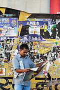A man reads a newspaper by a wall with political posters, New Delhi, India