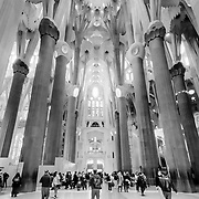 """Barcelona, Spain - February 20, 2018 - Tourists inside the Sagrada Familia in Barcelona, Spain. <br /> <br /> The ground breaking took place in 1882 and the structural work and decorations continue to this day. The designer of this amazing UNESCO World Heritage Site is Catalan architect Antoni Gaudi (1852-1926). On the subject of the extremely long construction period, Gaudi once remarked; """"My client is not in a hurry.""""<br /> <br /> Image: © Rod Mountain http://www.rodmountain.com<br /> <br /> @spain @barcelona_cat @visitbarcelona @basilicasagradafamilia <br /> <br /> @spain.info @bcn.cat @BasilicadelaSagradaFamilia @visitbarcelona<br /> <br /> @spain @barcelona_cat @sagradafamilia @VisitBCN_EN<br /> <br /> https://sagradafamilia.org<br /> https://en.wikipedia.org/wiki/Sagrada_Fam%C3%ADlia<br /> https://www.barcelona.cat/en/<br /> https://www.barcelonaturisme.com/wv3/en/<br /> https://www.spain.info/en/<br /> <br /> #documentaryphoto #ig_europe #bnw_europe #bw #enblancoynegro #flair_bnw #photo_colection_bw #bwsquare #bnw_society #bnw_universe #insta_bw #noir_vision #jj_blackwhite #sagradafamilia #creative_architecture #instagood #beautiful #europe_bnw #Spain #travelblog #trip #travelandlife #travels #getlost #travelingram #Gaudi"""