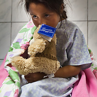 Elena waits for her operation that will cut through the webbing between her index and middle finger to correct a birth defect that has robbed her until now the ability to grasp objects, like crayons. Oregon orthopedic doctors and support staff helped hundreds of Peruvian children in Coya, Peru performing corrective surgeries and therapy to improve their quality of life.