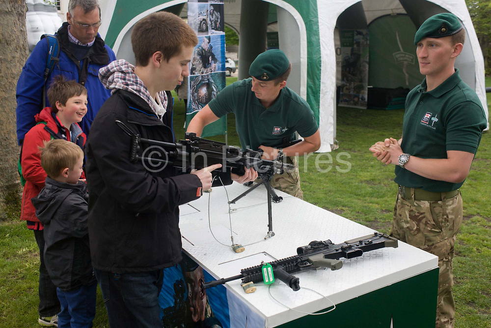 Members of Royal Marines Commandos demonstrate various weaponry to a teenage boy and smaller children during a public open-day in Greenwich, London during which the Royal Navy's aircraft carrier HMS Illustrious docked on the river Thames, allowing the tax-paying public to tour its decks before its decommisioning. Navy personnel helped with the PR event over the May weekend, historically the home of Britain's naval fleet.