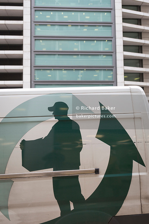 The graphic showing a person delivering a package, on the side of a courier's van, passing beneath corporate offices in the City of London, the capital's financial district, on 4th February 2020, in London, England. A man wearing a peaked cap is shown carrying a box with a large arrow pointing upwards to nearby offices.