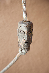 carved wooden head tied to a rope
