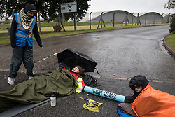 Farnborough, UK. 2nd October, 2021. Extinction Rebellion climate activists are pictured locked together using an arm tube in order to block an entrance to Farnborough Airport. Activists blocked three entrances to the private airport to highlight elevated carbon dioxide levels produced by super-rich passengers using private jets and 'greenwashing' by the airport in announcing a switch to sustainable aviation fuel (SAF).