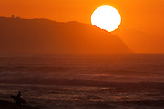 Sun setting behind Kaena Point and world famous surf on Oahu's North Shore, Hawaii.