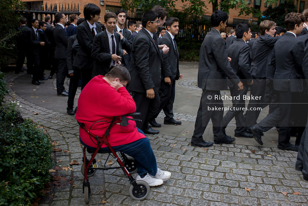 Schoolboys in grey suits walk past resting disabled woman.