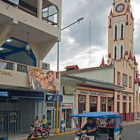 3-wheeled motocarros drive past a Catholic Church by the Plaza de Armas in Iquitos, Peru.