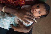 Rabari woman and child of the Sorathi subgroup found in and around the Gir Forest National Park Gujarat. W India. <br /> The women have very ornate earrings and many of them also have ornate tatoos on their necks, chests and arms. Designs such as peacocks and other religious symbols are usually done during festivals when the tatoo artists come to town.<br /> Locally these people are also known as Maldharis - which in their language means cattle herder.<br /> Rabari were traditionally camel herders but now each subgroup works with an animal that is most feasible in the surrounding environment. This subgroup are generally cattle herders. (Rabari is a term used for tribal livestock herders). As they live in and around the Gir Forest which is the home of the endangered Asiatic lion they loose a lot of their cattle to the lions. They are compensated however. Each costume varies slightly according to subgroup. The Sorathi Rabari man wear the 'Chorani' pants which are tight-calved with gathered waists. They also wear the 'Kediyun' men's short jacket that is tightly gathered at armpit level. These together with the turbin are made from white cotton. They also substitute the turban for woolen caps. In many cases the men also wear large ornate earings made from either gold. These are worn through the cartledge of the middle of the ear. Jewellery is their wealth and they never take it off.
