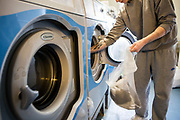 A prisoner using a washing machine on Beaufort House, a skill development unit for enhanced prisoners. Part of HMP/YOI Portland, a resettlement prison with a capacity for 530 prisoners.Dorset, United Kingdom.
