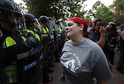 A woman pleads with Virginia State Police wearing riot gear to not attack the students during a student protest Saturday night at the University of Virginia. Photo/Andrew Shurtleff