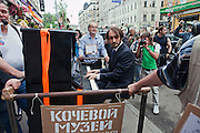 Moscow, Russia, 19/05/2012..A man plays a piano converted into a mobile artwork as several thousand artists and opposition activists demonstrate against Vladimir Putin by walking through Moscow transporting their artworks. The protest coincided with Museum Night, when Moscow's museums are open until midnight with special exhibitions and performances.